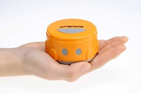 Automee S - Le Robot nettoyeur d'écrans iPhone et iPad dans une main. Couleur orange